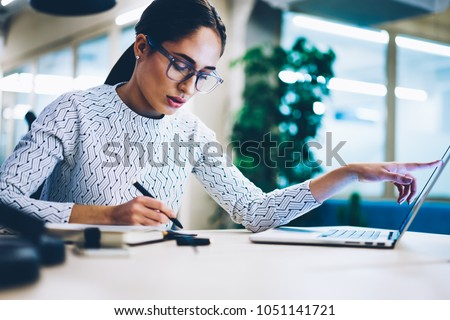 Pensive business woman noting idea for startup planning from web page on laptop computer,professional administrative manager making accountings of income using app on netbook in office interior #1051141721