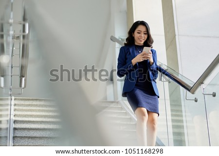 Smiling Asian manager in formalwear texting with friend on smartphone while going downstairs, portrait shot #1051168298