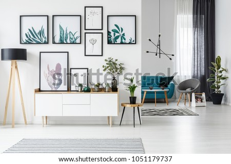 White living room interior with botanical posters on the wall and sofa in the background #1051179737