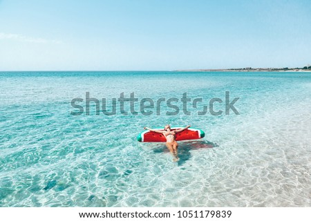 Woman on lilo in the sea water. Girl relaxing on inflatable ring on the beach. Summer vacations, idyllic scene. #1051179839