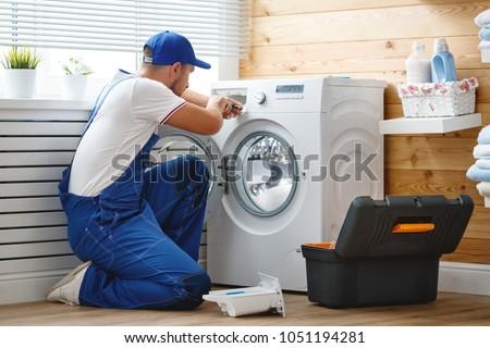 working man plumber repairs a washing machine in   laundry #1051194281
