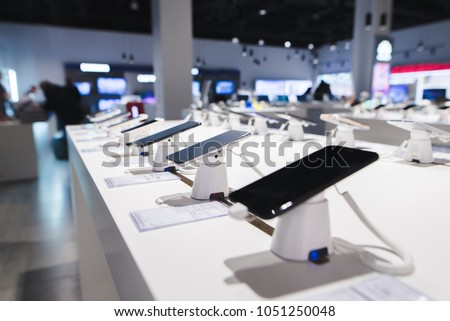 Smartphones on the background of the electronics store. Department of mobile phones in the tech store. A modern gadget store #1051250048