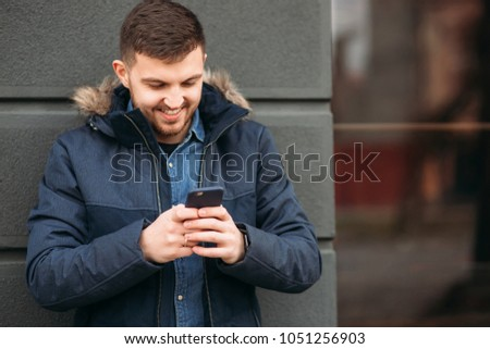 Handsome man in a jacket uses a phone standing on the street #1051256903