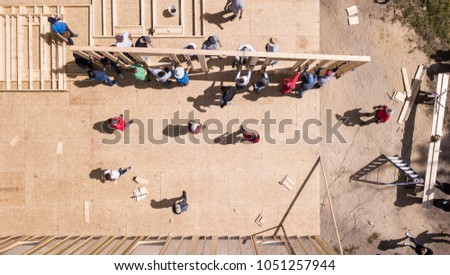 Top down view of workers raising a wall on construction of a new home. #1051257944