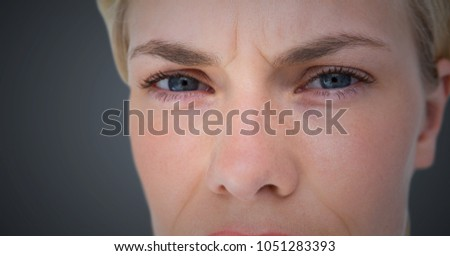 Digital composite of Close up of woman's angry eyes against grey background #1051283393
