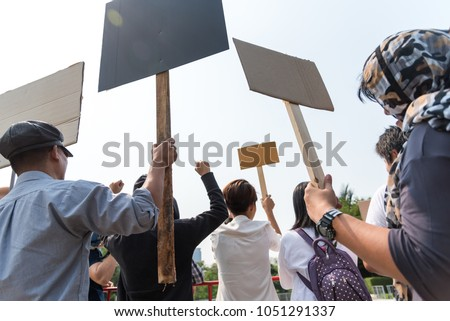 Men and women share a protest sign  hold a megaphone. Mob concept, The youth crowd gathered to protest. Royalty-Free Stock Photo #1051291337