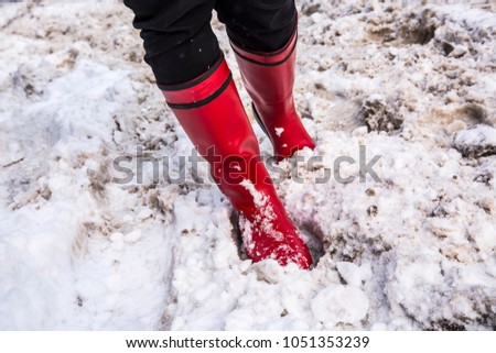 Girl in red boots in deep snow. Winter concept #1051353239