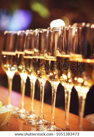 Sparkling wine glasses champagne stand in row at the bar, catering #1051383473