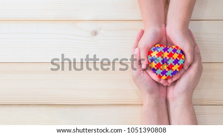 World Autism Awareness day, mental health care concept with puzzle or jigsaw pattern on heart with autistic child's hands supported by nursing woman, family caregiver person or parenting mother #1051390808