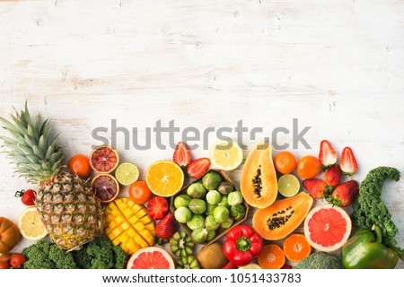 Fruits and vegetables rich in vitamin C, oranges mango grapefruit kiwi kale pepper pineapple lemon sprouts papaya broccoli, on wooden white table, top view, copy space, selective focus #1051433783