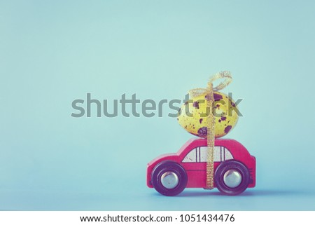 Easter holiday concept - Red toy car carrying yellow egg. Toned picture.