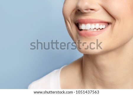 Young woman with beautiful smile on grey background. Teeth whitening #1051437563