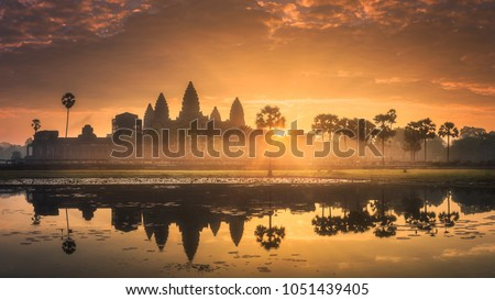 Sunrise view of popular tourist attraction ancient temple complex Angkor Wat with reflected in lake Siem Reap, Cambodia #1051439405