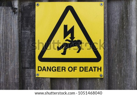 A yellow danger of death sign on a wooden fence.