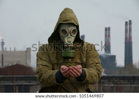 a man in a gas mask holds a plant germ, against a background of an industrial plant #1051469807