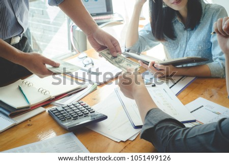 Professional investor meeting present time.Business partners meeting and passing money for new startup project in office room.Bribery and corruption concepts, estate concept, financial concept. #1051499126