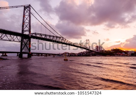 bridge Hercilio Luz Florianopolis Santa Catarina Brazil, image made from the island, showing the sunset. This bridge is from the beginning of the 20th century, does not have vehicular trafic  #1051547324
