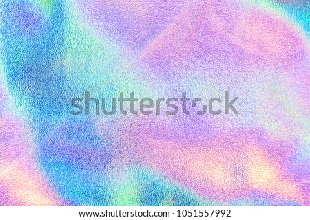 Holographic real texture in blue pink green colors with scratches and irregularities. Holographic color wrinkled foil. Holographic rainbow foil abstract background.