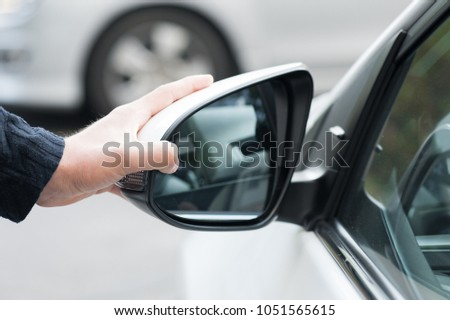 Young human hand is preparing or correct car mirror for the trip or travel from car window. #1051565615
