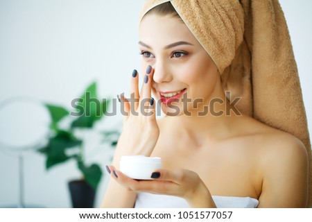 A beautiful woman asia using a skin care product, moisturizer or lotion and Skincare taking care of her dry complexion. Moisturizing cream in female hands #1051577057