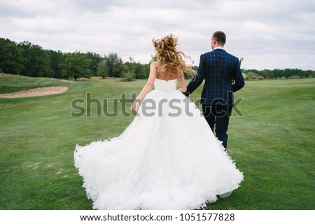Full length body portrait of young bride and groom running on green grass of golf course, back view. Happy wedding couple walking through golf course, copy space #1051577828