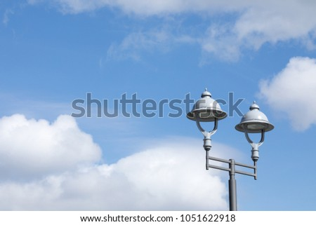 A pair of modern high efficiency LED street lamps, in front a bright cloudy blue sky background with space for text #1051622918