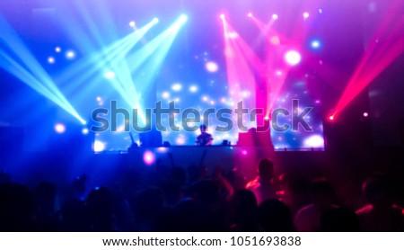 DJ turns music people dancing in night club with beautiful light, women and men in the happy fun.photo blur #1051693838