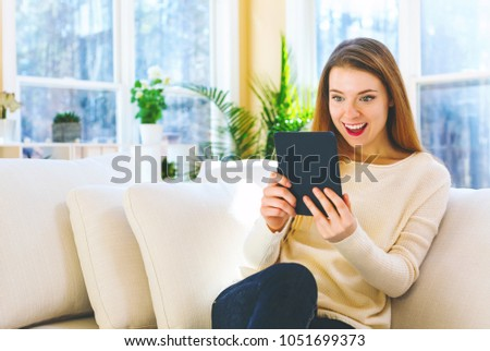Young woman reading with an e-reader in a large interior room #1051699373