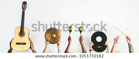 Hands holding music instruments Royalty-Free Stock Photo #1051710182