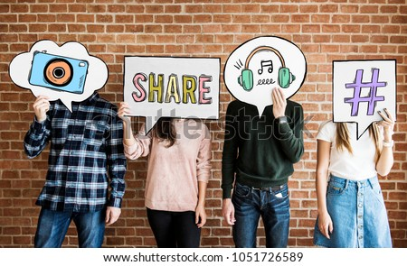 Friends holding up thought bubbles with social media concept icons #1051726589