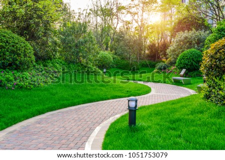 Pathways with green lawns, Landscaping in the garden,Top view of curve walkway on green grass field and flower garden  Royalty-Free Stock Photo #1051753079