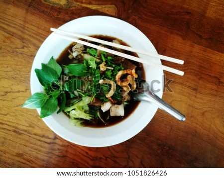 Stewed pork noodle in a white bowl on a traditional wooden table Rice noodle soup with stewed pork on table background. #1051826426