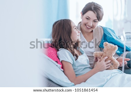 Sisters smiling and lying in bed in the hospital together. Family support during illness concept #1051861454