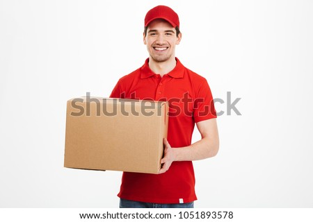Image of a happy young delivery man in red cap standing with parcel post box isolated over white background. #1051893578