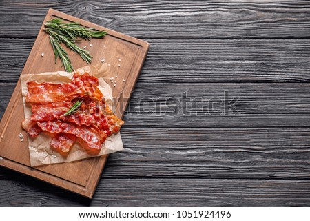 Board with fried bacon on wooden background
