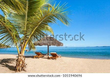 Two sunbeds under a straw umbrella on the tropical beach of Nosy Be, Madagascar #1051940696