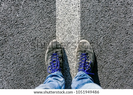Reaching a crossroads having to decide about past, now and future symbolized by two feet and shoes standing on two different colors on pathway from above #1051949486