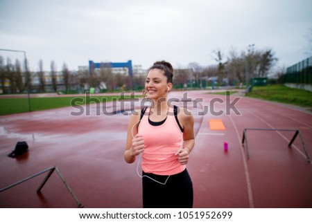 Portrait of attractive young happy fitness girl jogging while listening to music outside on running track. #1051952699