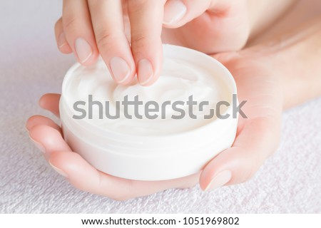 Beautiful groomed woman using moisturizing cream for clean and soft skin. Cream jar in hands above white towel. Healthcare concept. #1051969802