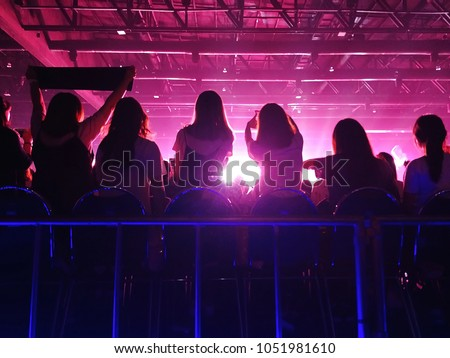 K-Pop music theme or live concert background silhouette of girls holding hands and sign for artist supporting. (space for text) Royalty-Free Stock Photo #1051981610