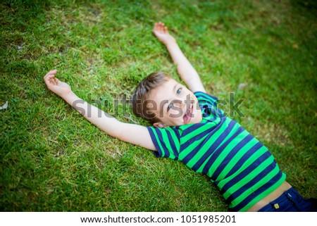 Little happy boy lies on the green grass #1051985201