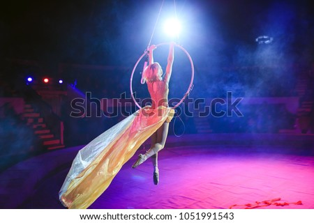 Aerial acrobat in the ring. A young girl performs the acrobatic elements in the air ring. Royalty-Free Stock Photo #1051991543