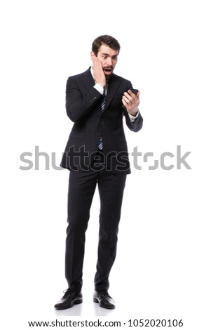 handsome business man looking shocked or worried at his mobile phone covering his face with his right arm isolated on white backround #1052020106