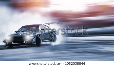 Car drifting, Blurred of image diffusion race drift car with lots of smoke from burning tires on speed track #1052038844