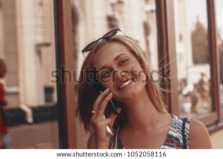 happy woman talking on the phone. on background is windows. blonde with short hair. #1052058116