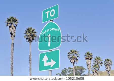Roadsign on highway one in California, USA with palm trees and sky Royalty-Free Stock Photo #105210608