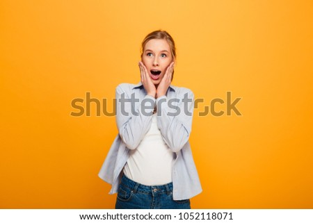 Portrait of a surprised young girl with braces looking at camera isolated over yellow background #1052118071