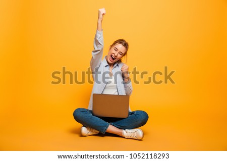 Portrait of a cheerful young girl with braces sitting on a floor with a laptop computer and celebrating success isolated over yellow background #1052118293