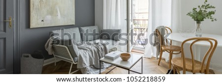 Gray living room with couch, table, modern painting and balcony, panorama #1052218859