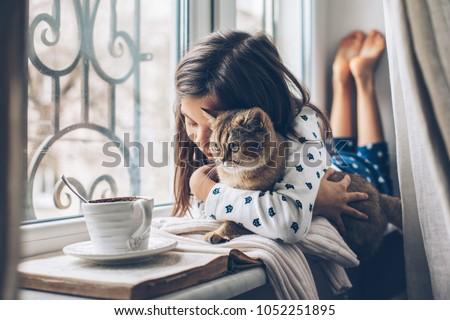 Child in pajamas relaxing on a window sill with pet. Lazy weekend with cat at home. Cozy scene, hygge concept. #1052251895